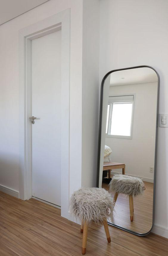 Detail of a bedroom with minimalist decoration: a full-length mirror reflects a stool.