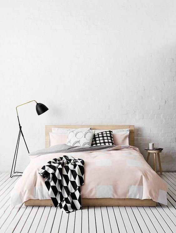 Minimalist bedroom: white floor and wall, a bed and a lamp on the side.